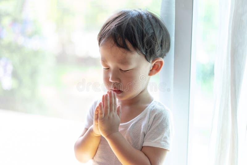 Uma oração pequena, um menino está rezando seriamente e esperançosamente a Jesus imagem de stock