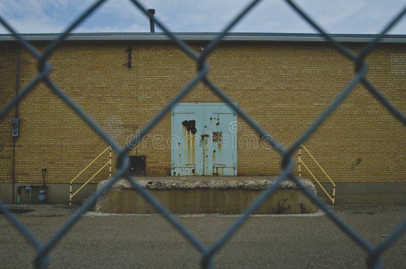 Uma oxidação e uma cerceta velhas coloriram a porta na parede velha da fábrica através da cerca fotografia de stock