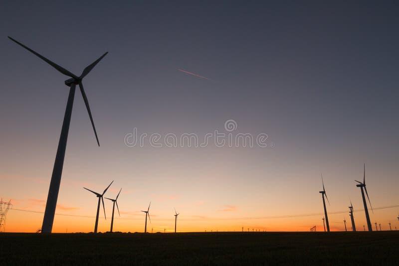 Uma paisagem com moinhos de vento em uma explora??o agr?cola de vento no por do sol que gera a fonte de energia alternativa e ver foto de stock