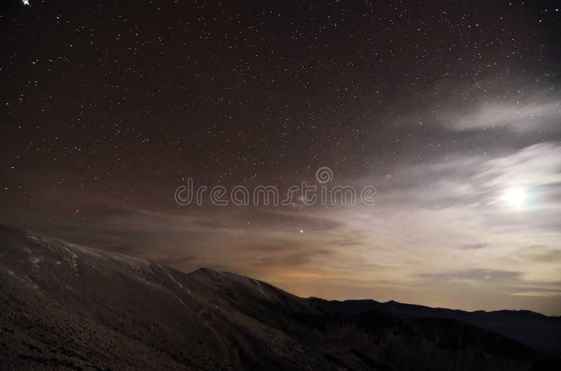 Uma paisagem das montanhas na noite com luar imagem de stock