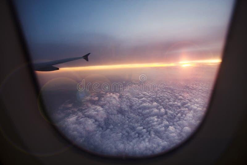 Uma paisagem do por do sol de uma janela do avião Peça da asa foto de stock royalty free