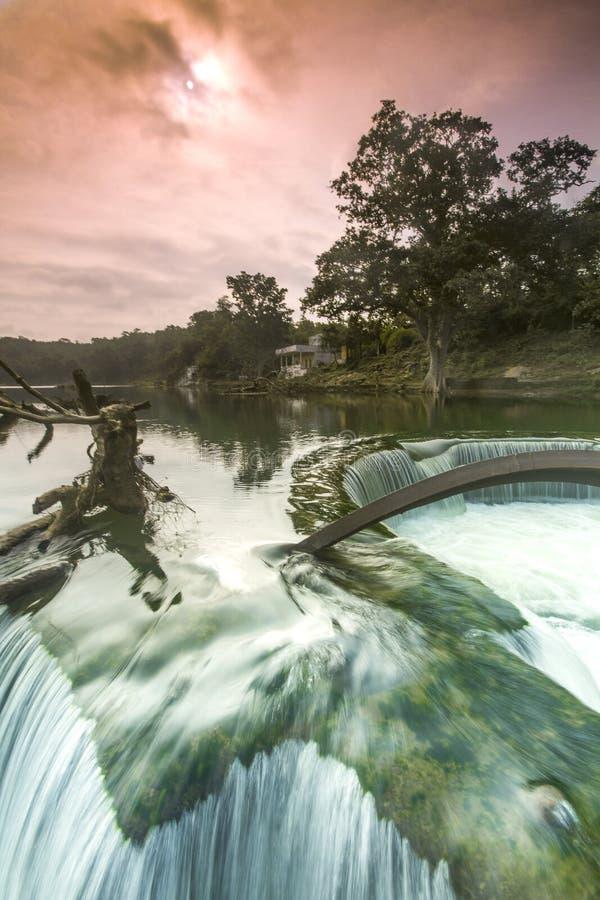Uma paisagem surreal colorida com árvore e água corrente caídas imagem de stock