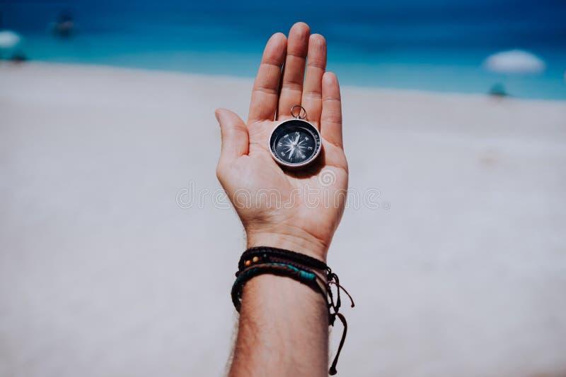 Uma palma esticada aberta da mão com compasso preto do metal no Sandy Beach Encontre seu conceito da maneira do objetivo do desej imagem de stock