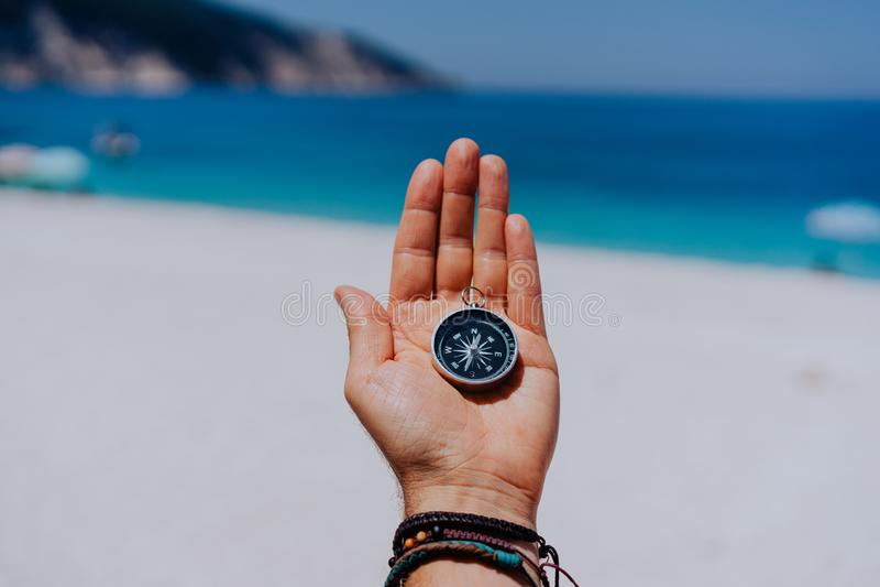 Uma palma esticada aberta da mão com compasso preto do metal no Sandy Beach Encontre seu conceito da maneira do objetivo do desej foto de stock