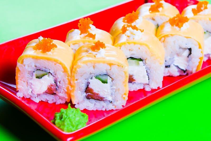 Uma parcela de sushi em uma placa vermelha Fundo verde foto de stock royalty free