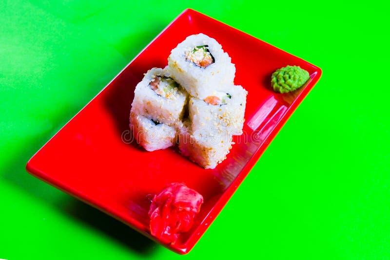 Uma parcela de sushi em uma placa vermelha Fundo verde fotografia de stock royalty free