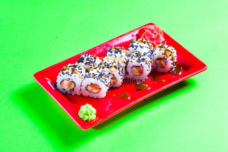 Uma parcela de sushi em uma placa vermelha Fundo verde imagem de stock royalty free