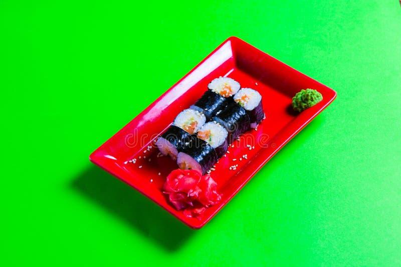Uma parcela de sushi em uma placa vermelha Fundo verde imagens de stock royalty free