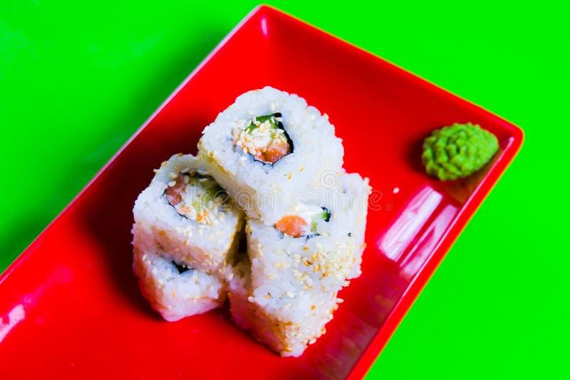 Uma parcela de sushi em uma placa vermelha Fundo verde fotografia de stock