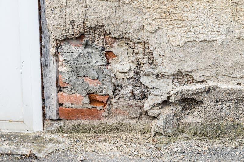 Uma parede danificada da casa e um emplastro exterior lascado com um grande furo, Alemanha imagem de stock