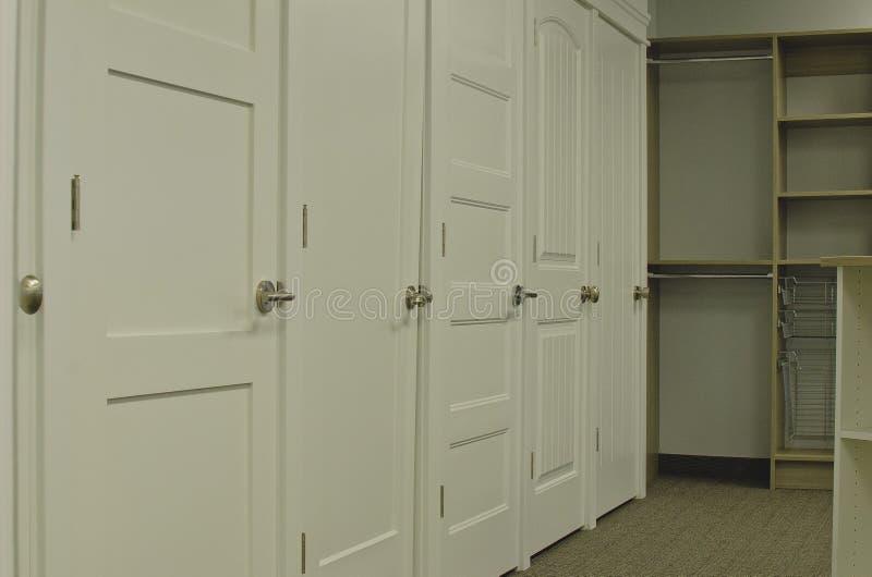Uma parede das portas e dos armários na sala de exposições foto de stock