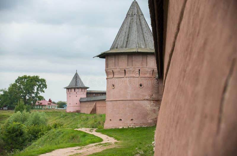 Uma parede de tijolo protetora alaranjada com as torres de observação na vila pequena fotografia de stock