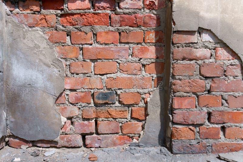 Uma parede de tijolo vermelho dilapidada em que o emplastro caiu o fragmento imagem de stock