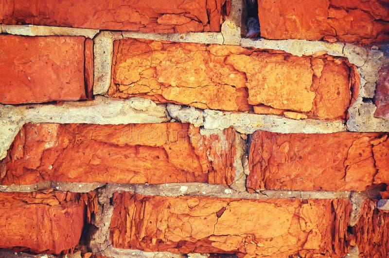 Uma parede de tijolo vermelho rachado do mau tempo foto de stock