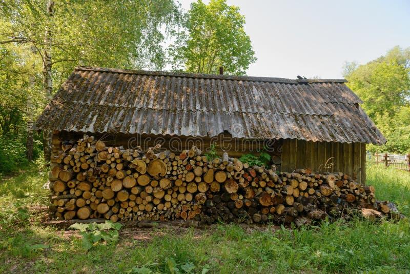Uma parede do log para a lenha em uma casa de madeira velha imagens de stock royalty free