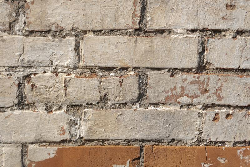 Uma parede dos tijolos tem sinais claros dos efeitos do tempo e de elementos naturais, almofariz de desintegra??o do cimento, pin foto de stock