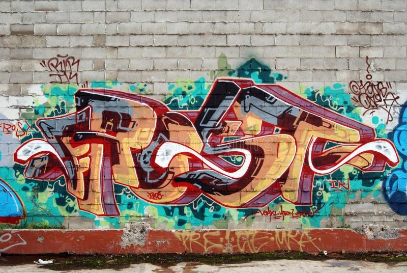 Uma parede vandalized com arte dos grafittis da rua imagens de stock