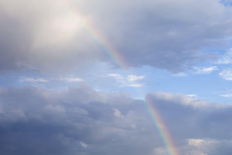 Uma parte bonita do arco-íris acima da floresta com nuvens cinzentas e um sol dourado imagem de stock royalty free