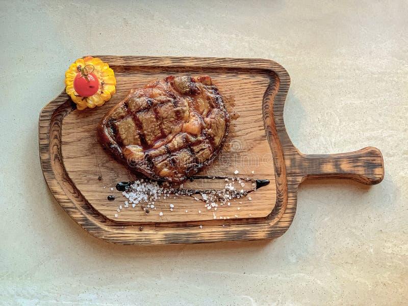 Uma parte de bife saboroso em um milho e em um tomate da placa fotografia de stock