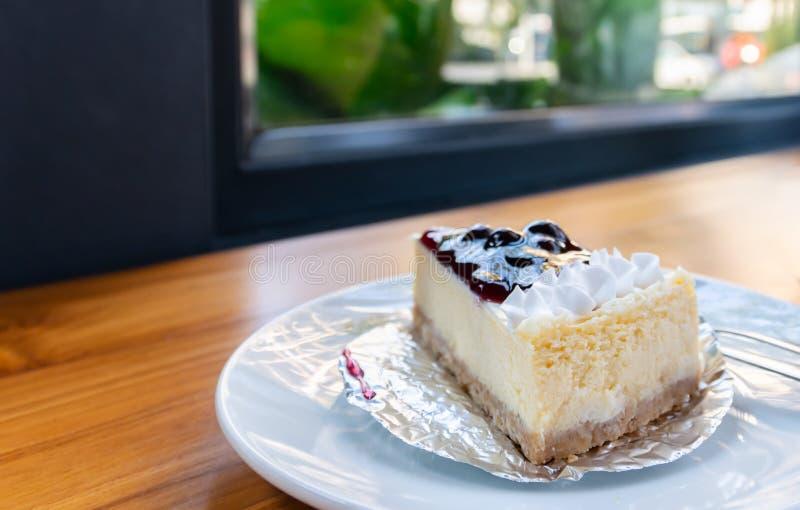 Uma parte de boca fresca que molha a torta caseiro do queijo do mirtilo na tabela de madeira imagem de stock