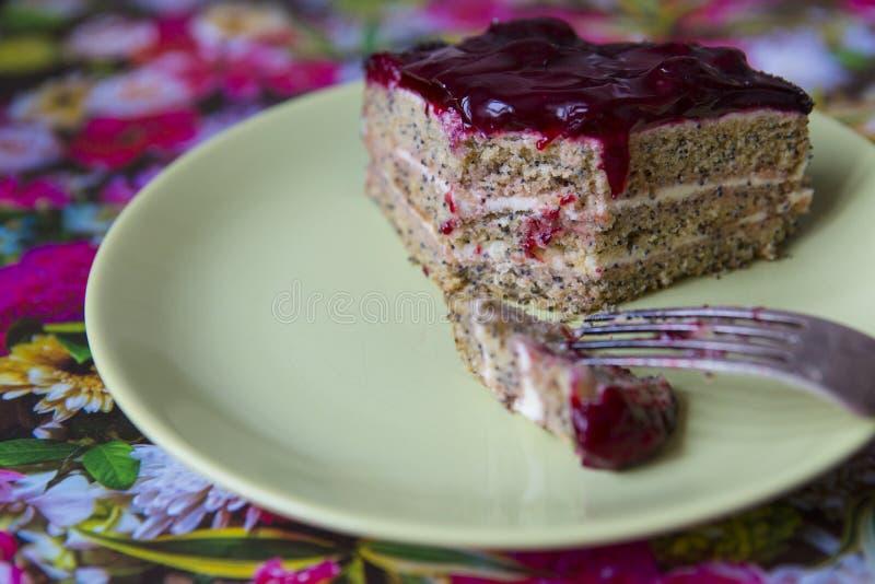 Uma parte de bolo da cereja da papoila em uma placa fotografia de stock