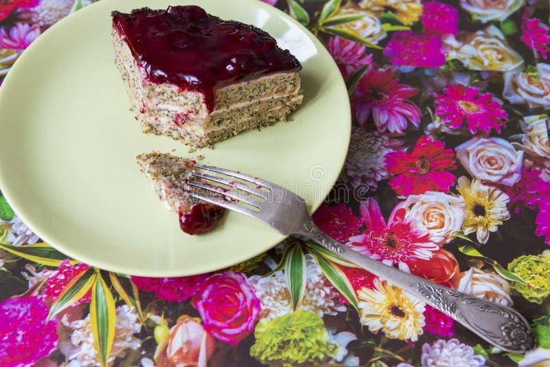 Uma parte de bolo da cereja da papoila em uma placa foto de stock