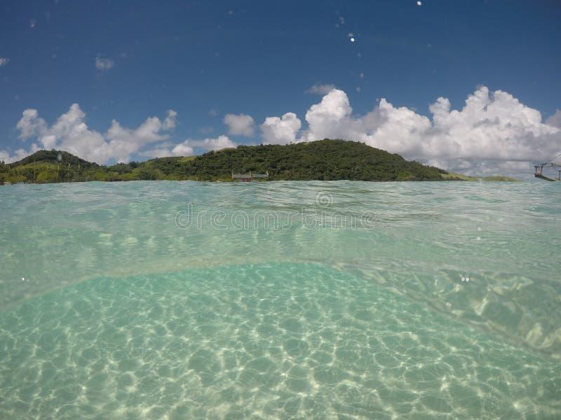Uma parte de continente, ilha pequena que flutua sob as águas claras imagens de stock