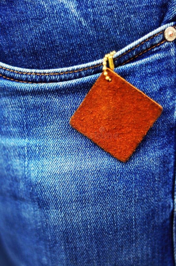 Uma parte de couro no fundo de calças de ganga imagens de stock