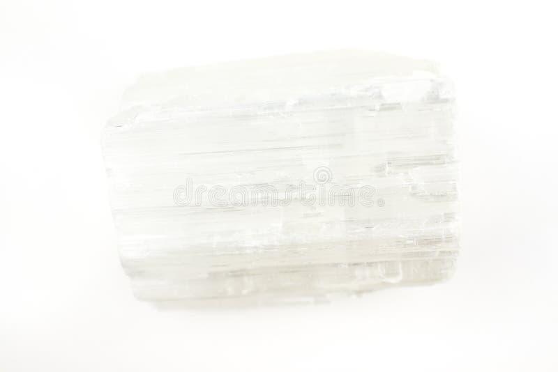 Uma parte de cristal do selenito em um fundo branco fotografia de stock royalty free