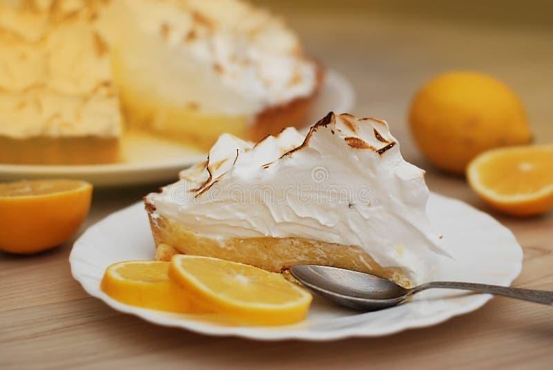 Uma parte de galdéria do limão com merengue Caramelized o creme na placa no fundo de madeira branco imagens de stock royalty free