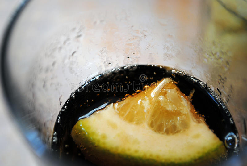 Uma parte de limão no vidro com cola imagem de stock royalty free