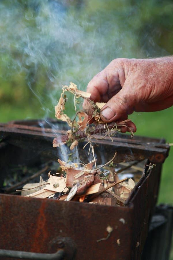 Uma parte de madeira das posses masculinas da mão sob o começo da inflamação um fogo do acampamento fotos de stock royalty free