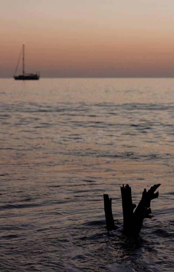 Uma parte de madeira lançada à costa no primeiro plano e de um barco no fundo em Tonga foto de stock