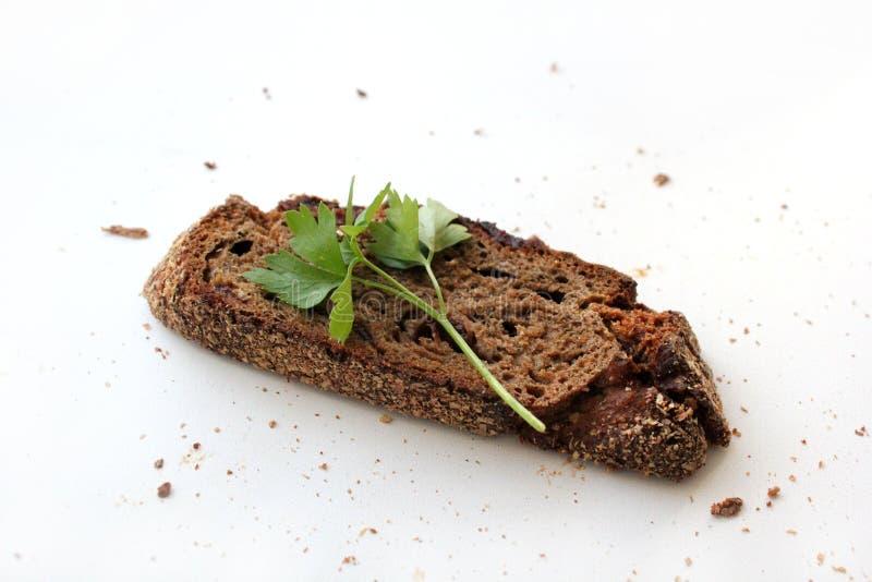 Uma parte de pão escuro com arandos e um ramo da salsa em um fundo branco com espaço livre para o texto imagens de stock royalty free