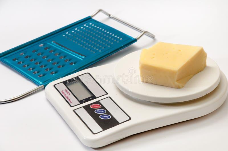 Uma parte de queijo amarelo em uma escala digital da cozinha com ralador imagens de stock royalty free
