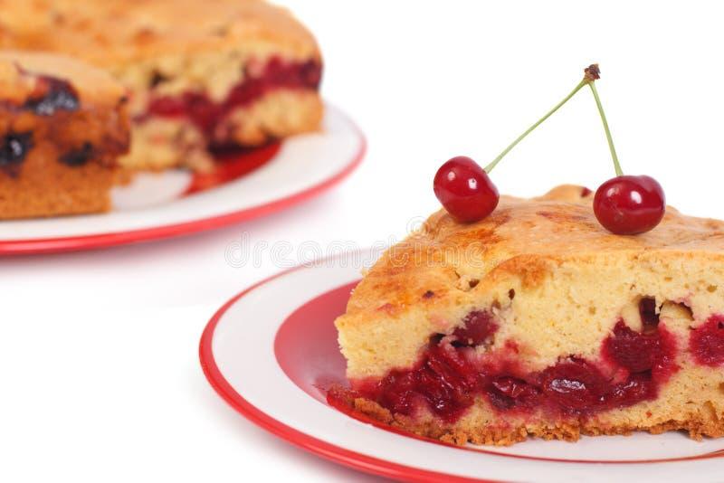 Uma parte de torta da cereja em uma placa isolada no branco imagem de stock royalty free
