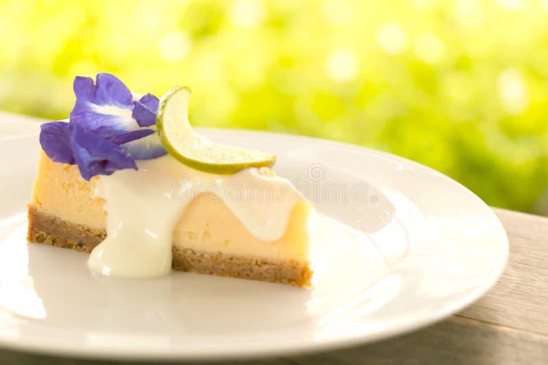 Uma parte de torta deliciosa do queijo do limão na placa branca na tabela de madeira fotografia de stock