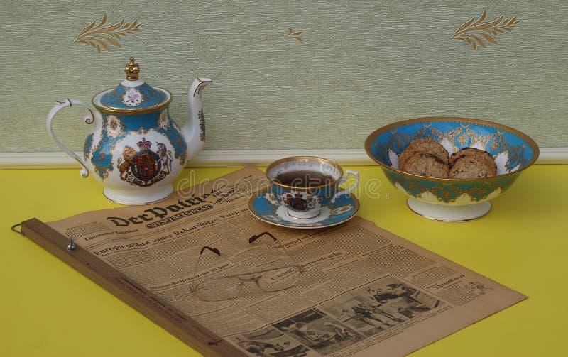Uma parte de um grupo de chá inglês e vidros de leitura em um patriota alemão idoso de Der do jornal, edição de 8 Em junho de 195 fotografia de stock