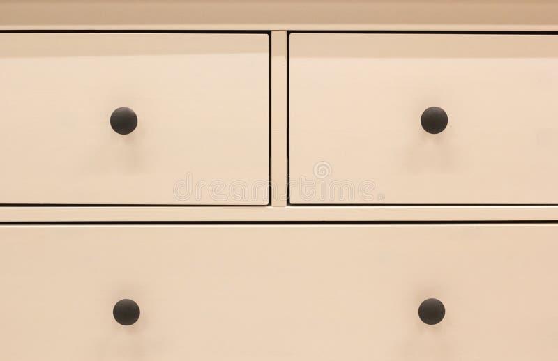 Uma parte dianteira de madeira da gaveta do vestuário, punho do metal, close-up fotografia de stock royalty free