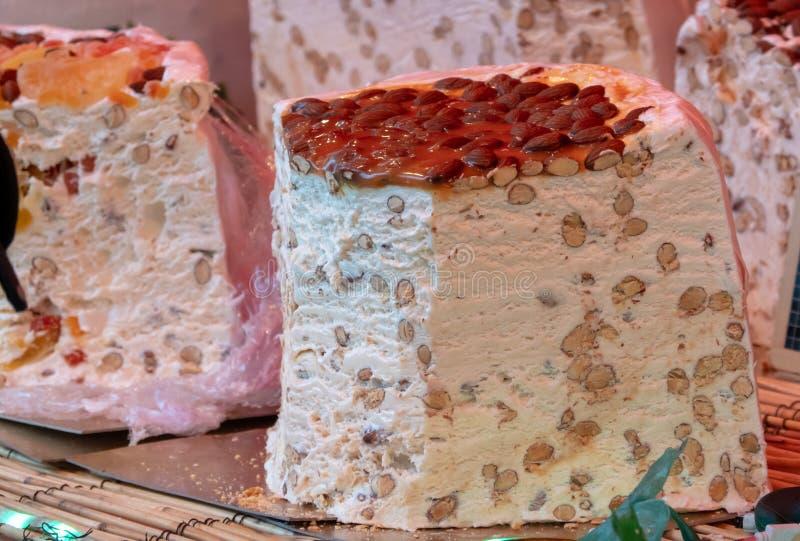 Uma parte enorme de nougat branco francês com amêndoas e partes inteiras da noz imagens de stock