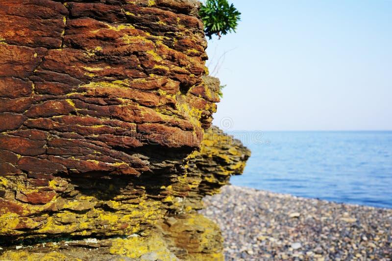 Uma parte grande do close up vermelho-marrom da rocha contra o mar azul foto de stock