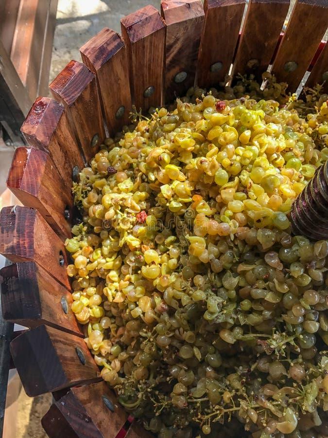 Uma parte superior abaixo da vista tambor de madeira antiquado de uma imprensa dada forma da uva completamente das uvas imagem de stock royalty free