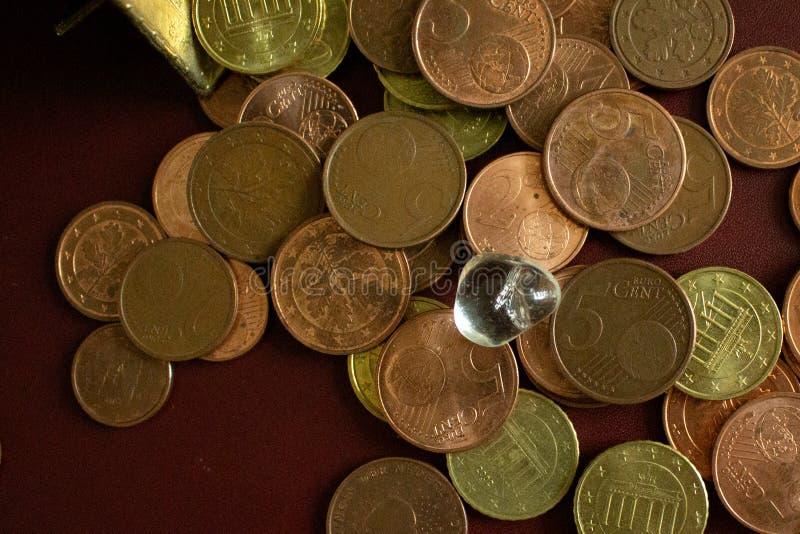 Uma pedra preciosa de cristal clara pequena em um montão de moedas de ouro do dinheiro fotografia de stock royalty free