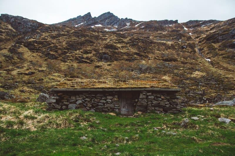Uma pedra velha pequena e uma casa de madeira cobertas com o musgo no fundo das montanhas imagem de stock