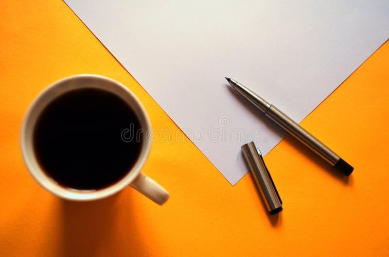 Uma pena aberta e uma xícara de café, durante uma ruptura do trabalho imagens de stock