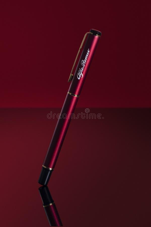 Uma pena vermelha de romeo do alfa suspendida com fundo vermelho imagem de stock