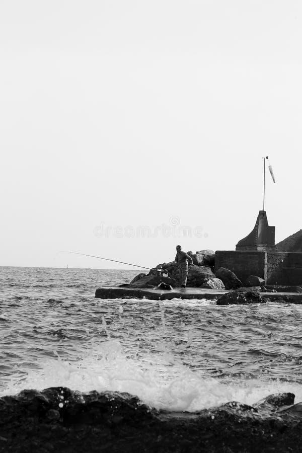 Uma pesca da pessoa do molhe concreto com as ondas que espirram nas rochas imagens de stock royalty free