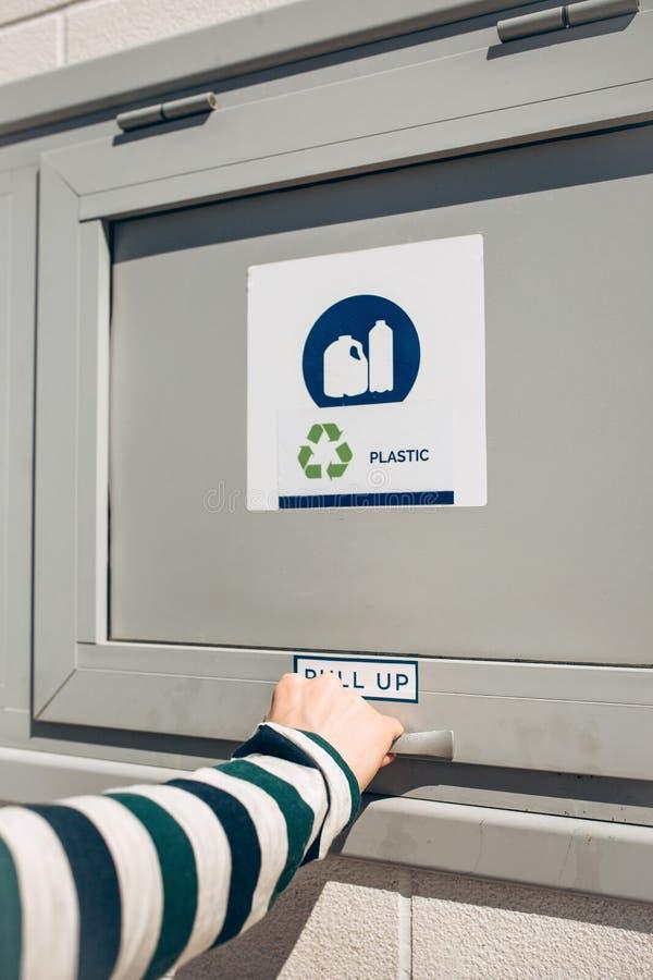Uma pessoa abre um escaninho de desperdício moderno imagem de stock