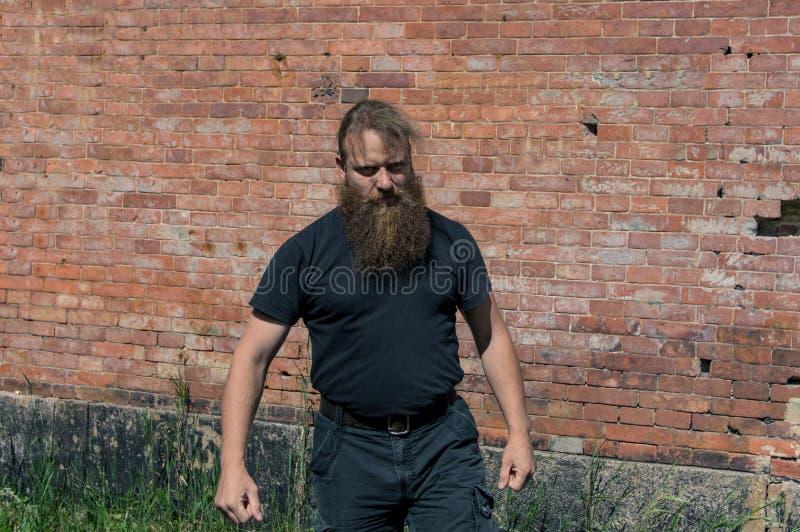 Uma pessoa agressiva com uma barba no movimento imagem de stock
