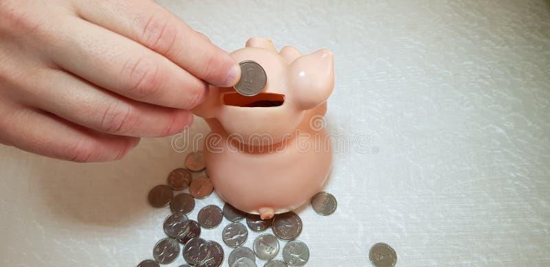 Uma pessoa caucasiano põe uma moeda israelita do shekel no mealheiro de salvamento foto de stock royalty free